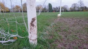 A close up of muddy football goal posts. Soccer field green grass brown mud white line mouth between the sticks over on resting netting score saved floor turf Royalty Free Stock Photo