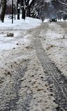 City street under dirty snow. Close up of muddy street surface and tire trucks. Blizzard in NW Chicago suburb, February 2018 Royalty Free Stock Image