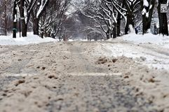 City street under dirty snow. Close up of muddy street surface and tire trucks. Blizzard in NW Chicago suburb, February 2018 Royalty Free Stock Photo