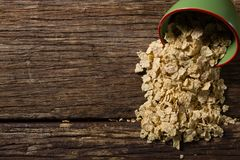 Muesli spilling from bowl on the wooden table Royalty Free Stock Photography