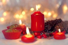 Close up of muffins in a red wrapper with red candles and holiday wreath. Bokeh background with a shallow depth of field. Stock Photos