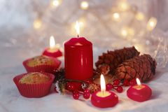 Close up of muffins in a red wrapper with red candles and holiday wreath. Bokeh background with a shallow depth of field. Royalty Free Stock Images