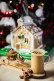 Close-up mug with coffe and milk on a wooden table, gingerbread house and christmas lights and decorations on bokeh royalty free stock image