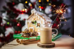 Close-up mug with coffe and milk on a wooden table, gingerbread house and christmas lights and decorations on bokeh. Sparkler royalty free stock photo
