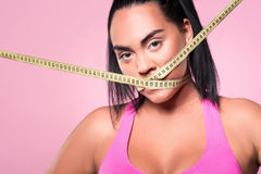 Close-up of mulatto woman covering mouth with measuring tape Royalty Free Stock Photos