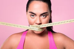 Close-up of mulatto woman covering mouth with measuring tape Stock Photography