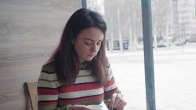 Close-up, mulher bonita em uma camiseta que come o bolo em um café e em olhares do inverno pensativamente para fora a janela video estoque