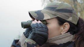 Close-up, mulher bonita na camuflagem do exército com os binóculos no rio no amanhecer da névoa video estoque
