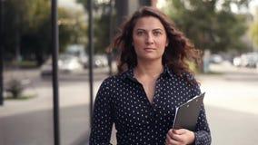 Close-up A mulher de negócio bonita vai trabalhar perto de um prédio de escritórios com originais nas mãos vídeos de arquivo