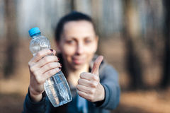 Close-up, mulher que guarda uma garrafa de água e que mostra o polegar acima? utdoors Foto de Stock
