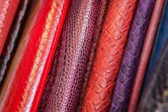 Pattern made of genuine leather. A close-up of multi-colored natural leather: red, purple, blue under the skin of snakes and reptiles. Pattern made of genuine Royalty Free Stock Images