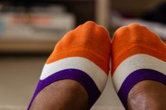 Close up of multi-colored socks on a black woman. Close up of multi-colored socks on the feet of a black woman royalty free stock images