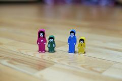 Close-up multi-colored wooden figurines of a family with two children on a wooden floor background. father with daughter, mother w royalty free stock image