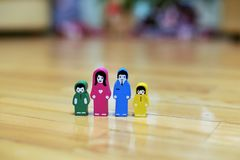 Close-up multi-colored wooden figurines of a family with two children on a wooden floor background. parents together, children fro. Close-up multi-colored wooden royalty free stock photography