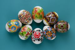 Close-up of multicolored traditional motifs on Easter eggs. Festive card of colorful easter eggs on blue background. Copy space. stock photography