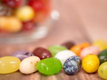 Jelly Beans in  jar. Close up of multicoloured jelly beans in a glass on a wooden background Stock Image