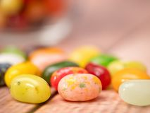 Jelly Beans in  jar. Close up of multicoloured jelly beans in a glass on a wooden background Stock Photo