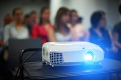 Close-up multimedia projector with blurred people background. Unrecognazible people royalty free stock photos