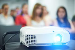 Close-up multimedia projector with blurred people background. Unrecognazible people royalty free stock image