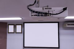 Close up Multimedia projector installed on the ceiling.  stock image