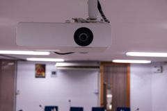 Close up Multimedia projector installed on the ceiling.  royalty free stock image