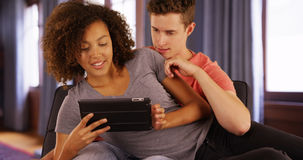 Close-up of multiracial couple using tablet computer to look online. Stock Images