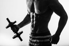 Close up of muscular bodybuilder guy doing exercises with weights dumbbell over isolated light background. Black and Royalty Free Stock Photography