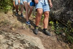 A close-up of muscular legs of young people going down the hill. A company of sportive travelers on a blurred natural royalty free stock image