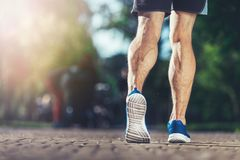 Well shaped athlete jogging in park. Close up of muscular male feet. Fit man is running in morning preparing for competition. Copy space in left side Stock Photos