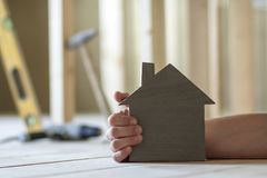 Close-up of muscular male hand holding small model house on blurred background of building tools in room under construction. Inves. Tments in real estate Royalty Free Stock Photography