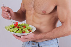 Close up of muscular man eating salad. Healthy life style, vegetarian bodybuilding concept. Stock Photography