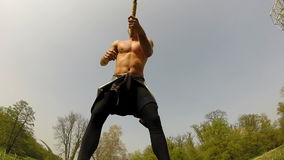 Close up of a muscular man hitting with a hammer, changing hands stock video