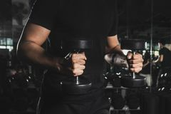 Close Up of a muscular young man lifting weights in gym on dark background. royalty free stock photos
