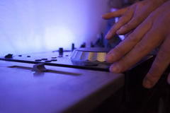 Close up of a music dj mixing tracks on his electronic console Royalty Free Stock Photography