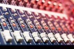 Close-up of music mixer in audio studio. With red lights from nightclub stock illustration