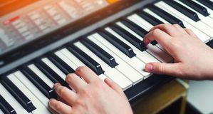 Close-up of a music performer`s hand playing the piano, man`s hand, classical music, keyboard, synthesizer, pianist.  Stock Photos