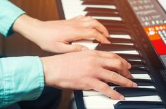 Close-up of a music performer`s hand playing the piano, man`s hand, classical music, keyboard, synthesizer, pianist.  Stock Image