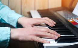 Close-up of a music performer`s hand playing the piano, man`s hand, classical music, keyboard, synthesizer, pianist.  Royalty Free Stock Photos