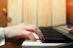 Close-up of a music performer`s hand playing the piano, man`s hand, classical music, keyboard, synthesizer, pianist.  Royalty Free Stock Photo