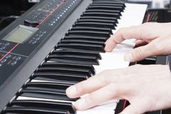 Close-up of a music performer`s hand playing the piano, man`s hand, classical music, keyboard, synthesizer, pianist. Close-up of a music performer`s hand Royalty Free Stock Photo