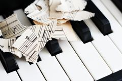 Close-up music score on piano keyboard, piece of paper. Object Stock Image