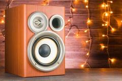 Close-up musical do orador em um fundo de madeira Festões de incandescência no fundo Imagens de Stock