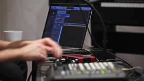 Close up of musician playing midi keyboard in home music studio. Close up of professional musician recording midi keyboard in digital studio at home. He is