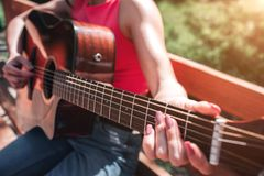 Close up of musician`s hands playing the guitar. Girl is holding her fingers on guitar`s strings. Girl is sitting on. Bench outside in this beautiful day royalty free stock photography
