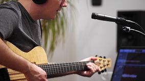Close up of musician singing and playing electric guitar in home music studio. Close up of musician recording electric guitar in digital studio at home. He is stock video footage