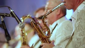 Close-up. The musicians  in white clothes play saxophones. The musicians of the brass band in white clothes play saxophones. Close-up. Small DOF stock video