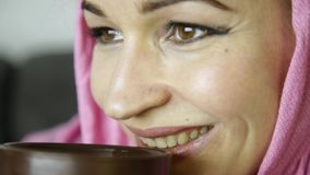 Close-up of muslim girl in pink hijab drinks coffee. Close-up of muslim woman in pink hijab drinks coffee stock footage