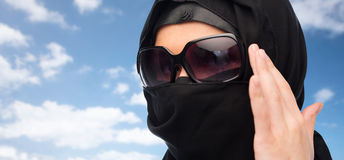 Close up of muslim woman in hijab and sunglasses. Accessory, fashion and people concept - close up of muslim woman in hijab and sunglasses over blue sky and Royalty Free Stock Image