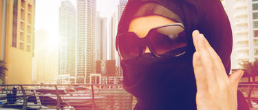 Close up of muslim woman in hijab and sunglasses. Accessory, fashion and people concept - close up of muslim woman in hijab and sunglasses over dubai city street Stock Photos