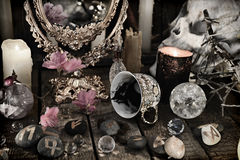 Close up of mystic objects, skull and pink flowers. Halloween background, black magic rite or spell, occult and esoteric objects on witch table stock photography